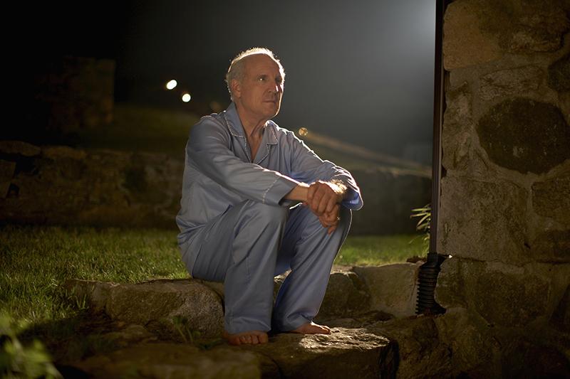 Senior man in pajamas sitting outside house at night