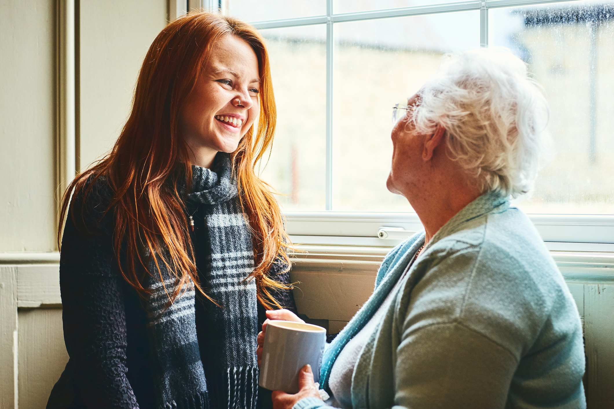 Young woman talks to senior woman about home health solutions.