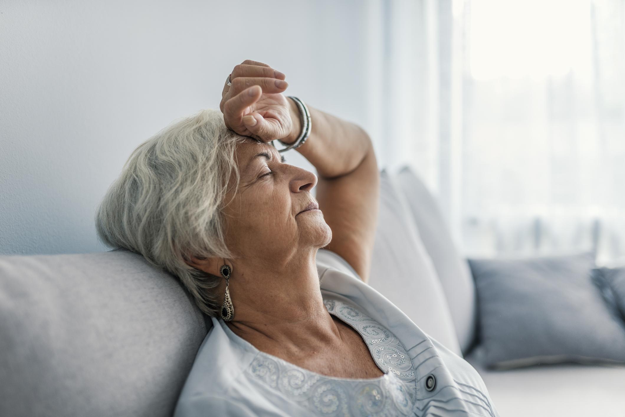 Elderly woman experiencing extreme senior fatigue.