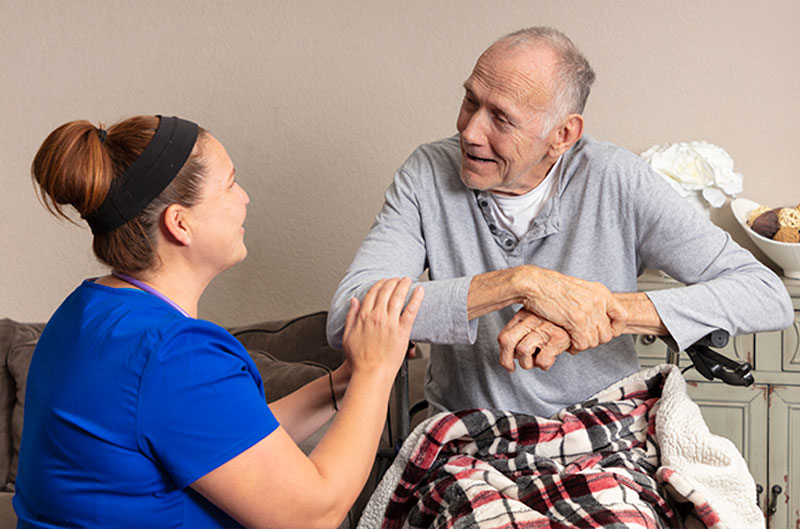 home caregiver comforting senior man on Hospice