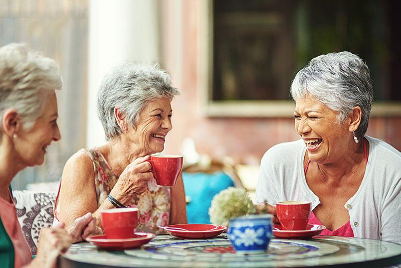 social wellness - 3 happy ladies having coffee