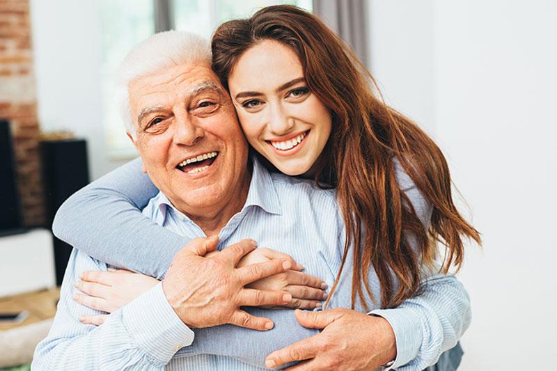 family-caregiver-hugging-senior-with-parkinsons
